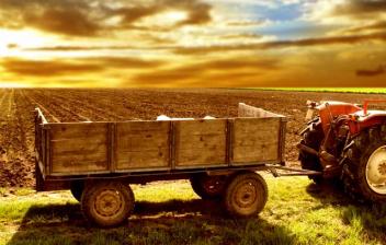 Tractor rojo con remolque en el campo