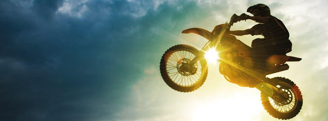 Hombre en una moto de motocross con el cielo de fondo