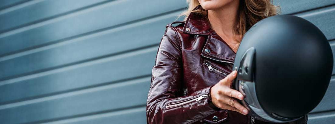 Mujer quitándose el casco de la moto