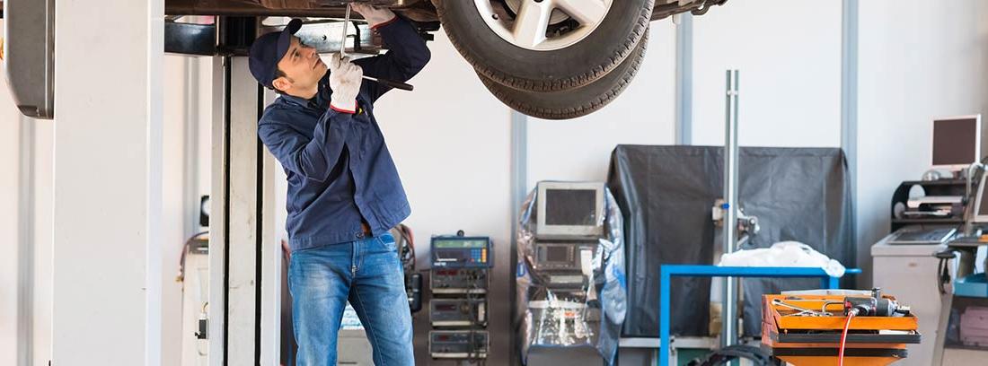 Mecánico revisando la transmisión de un vehículo