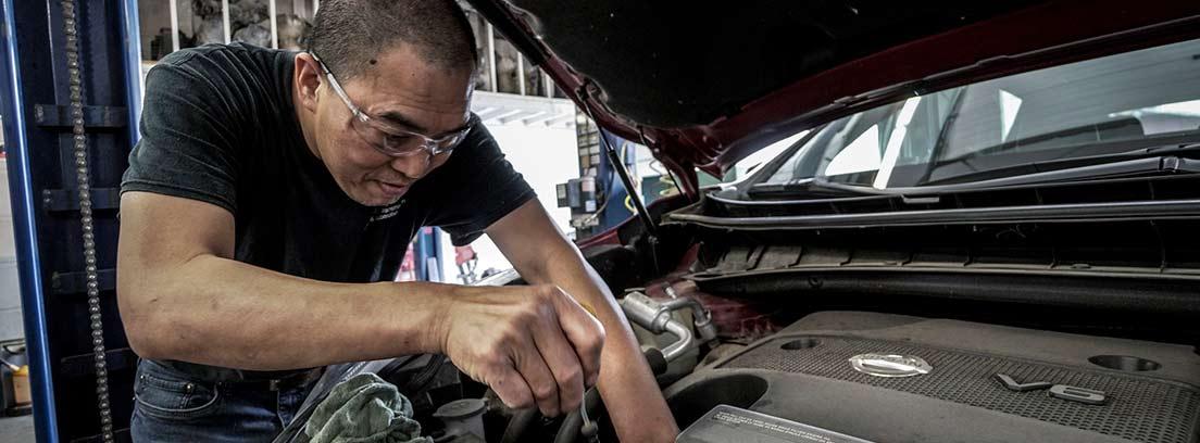 Mecánico con destornillador reparando el motor de un coche con tapa