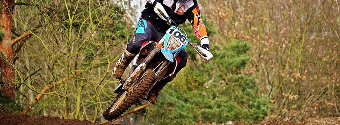 Motorista en una moto enduro en el campo