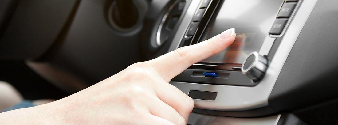 Mano tocando la pantalla de una radio de coche