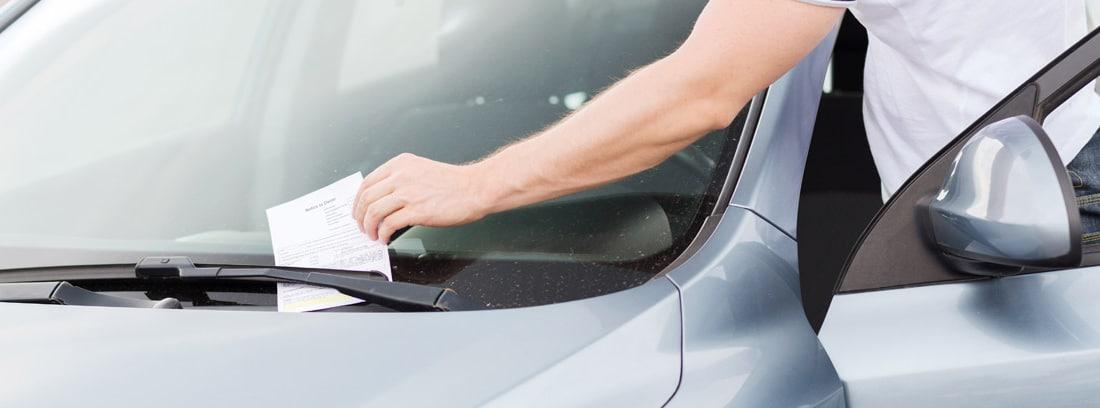 Hombre entrando en un coche mientras coge una multa del limpiaparabrisas