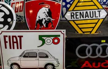 Carteles con los emblemas de varias marcas de coche y moto