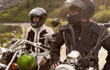 Pareja de moteros con el casco puesto con un fondo de montaña
