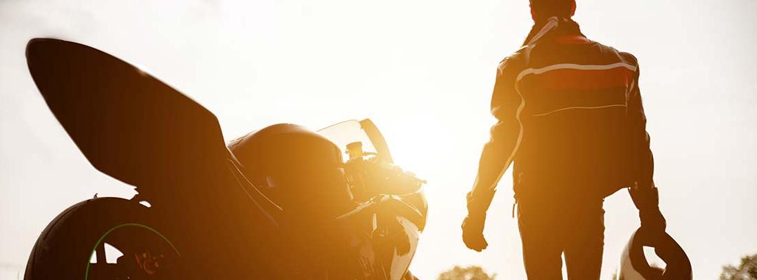 Hombre de espaldas con el casco en la mano junto a su moto en el campo