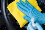 Manos con guantes limpiando el interior de un coche