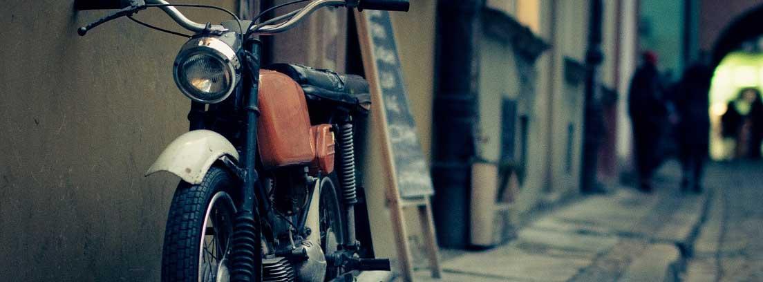 Moto antigua aparcada en una acera