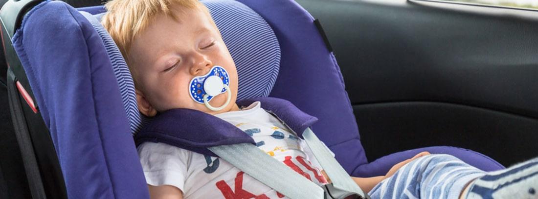Bebé dormido en un coche con un parasol en la ventana