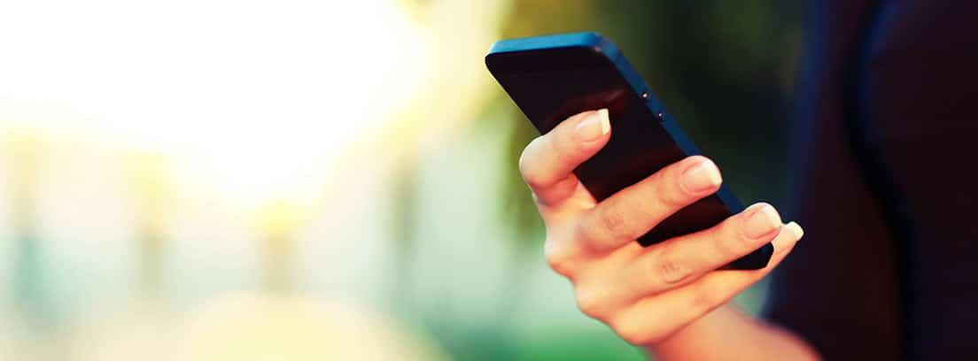 Mano sosteniendo un móvil en la calle
