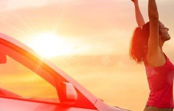 Mujer con los brazos en alto en una puesta de sol junto a un coche