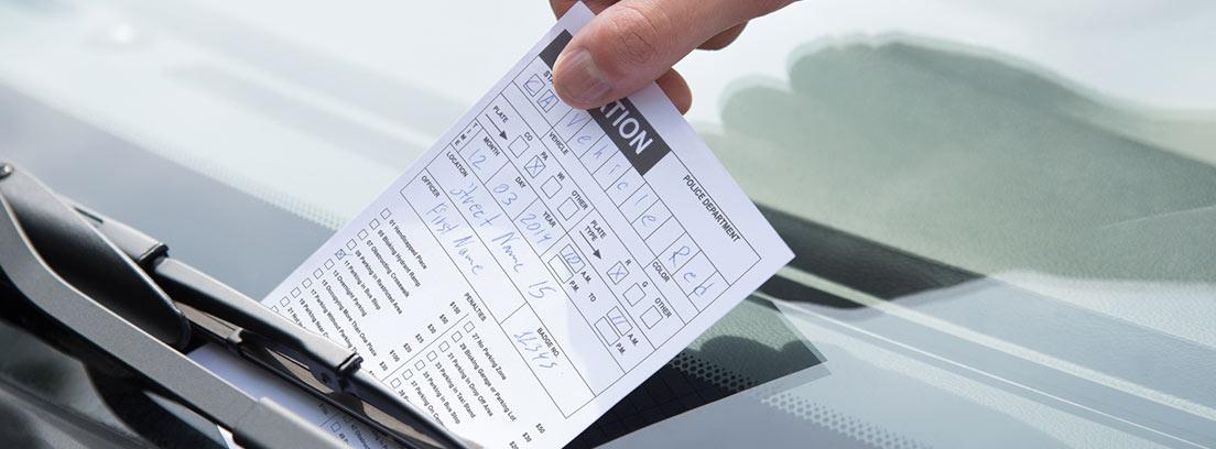 Mano retirando una multa del parabrisas de un coche