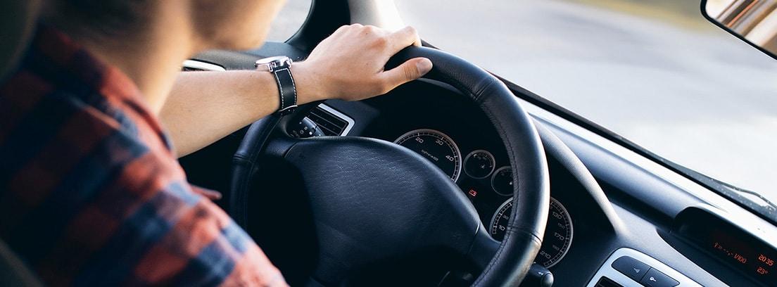 Joven sentado al volante de un coche