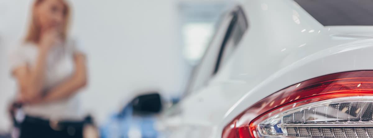 Primer plano del foco trasero de un coche y mujer pensativa