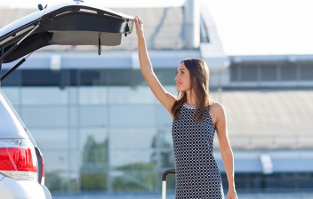Mujer cerrando el maletero de su vehículo aparcado