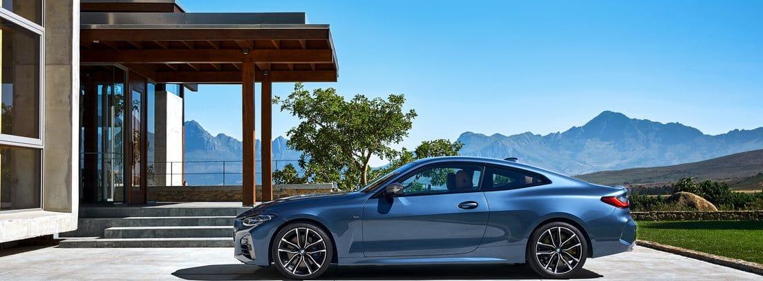 Vista lateral del BMW Serie 4 Coupé aparcado con una montañas al fondo