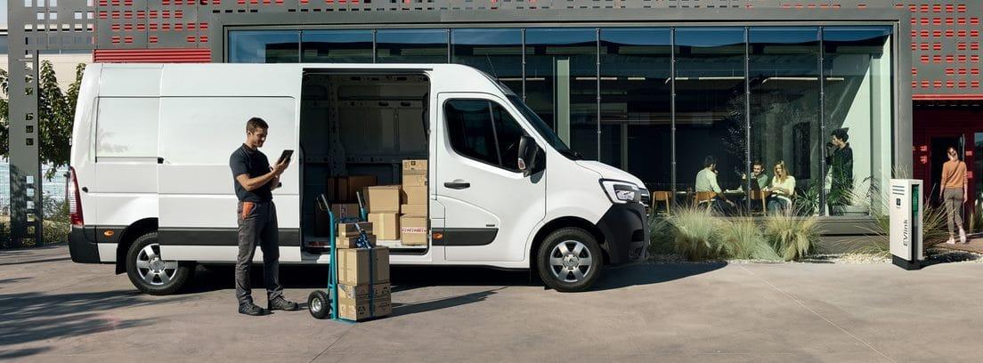 Profesional junto al furgón Renault Master ZE con el portón lateral abierto y cajas de cartón en su interior