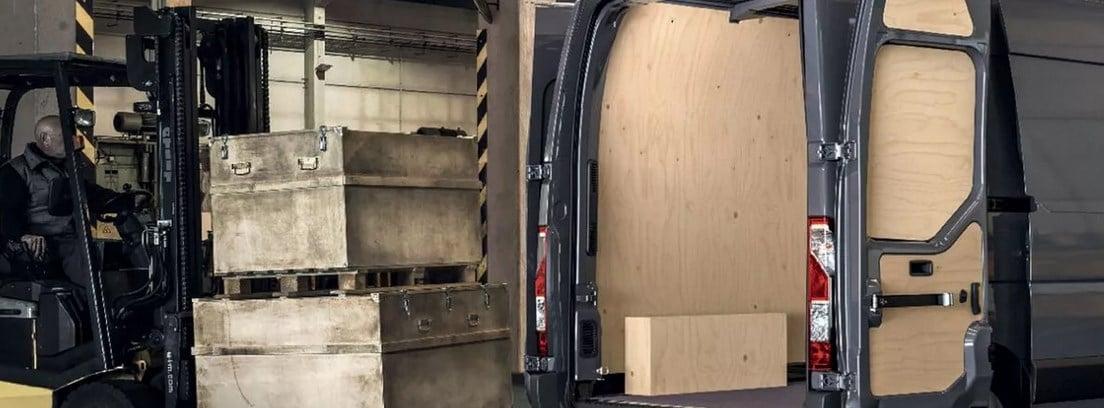 Carretilla elevadora con cajas de madera junto a un furgón con el portón trasero abierto y revestido de madera