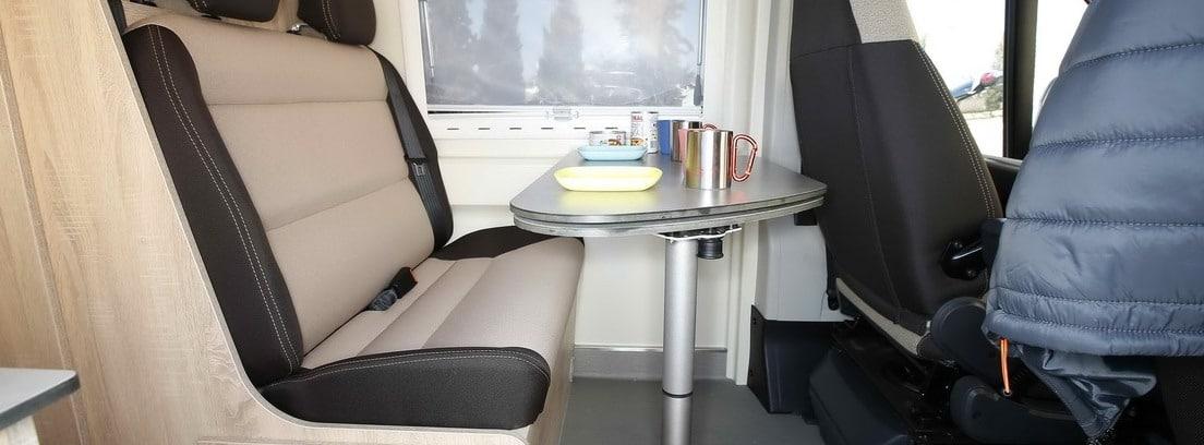 Interior de un vehículo camperizado con una mesa preparada para comer
