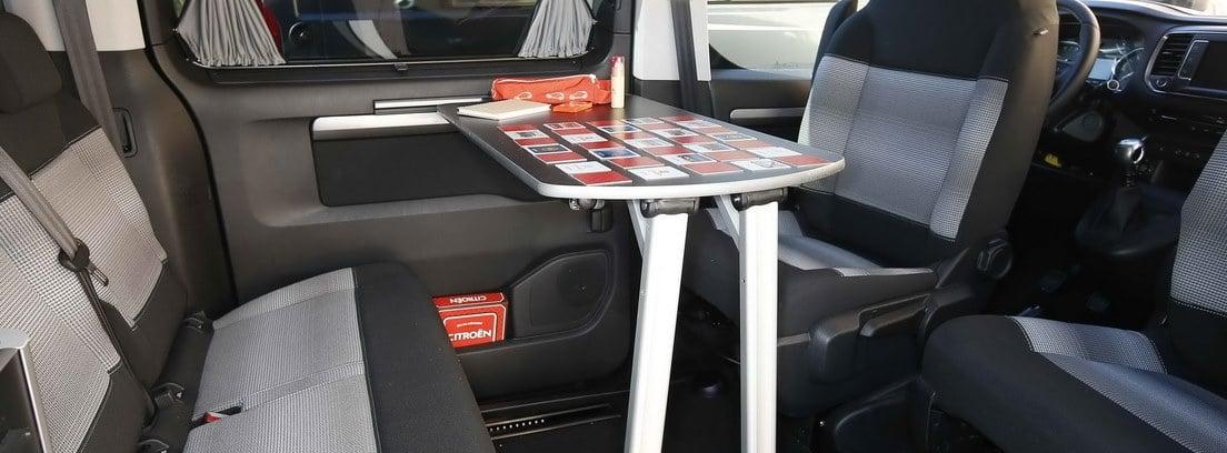 Interior de un vehículo camperizado con una mesa de juegos desplegada entre los asientos girados