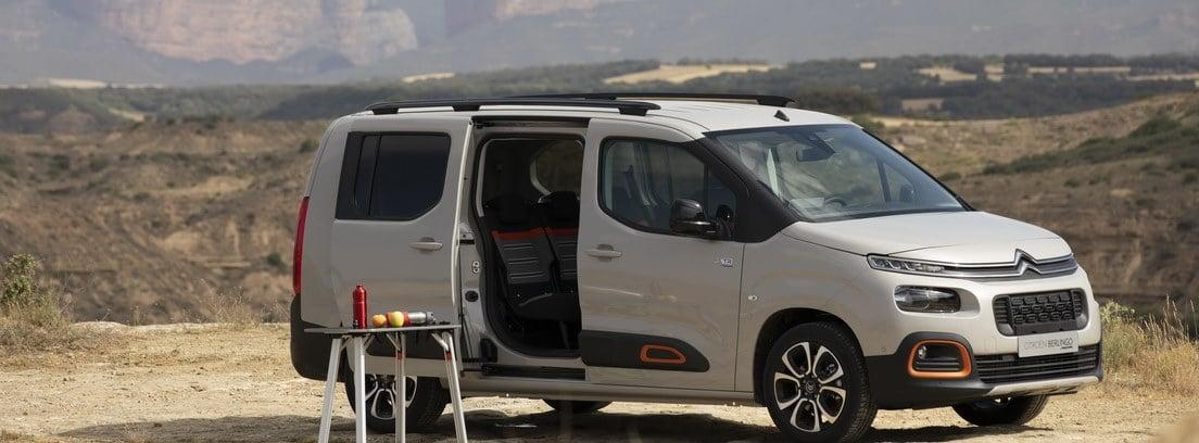 Furgoneta Citroën parada sobre tierra con el portón lateral abierto y una mesita de camping desplegada con objetos encima