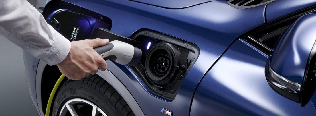 Hombre con camisa blanca a punto de enchufar el BMW X2 xDrive25e azul