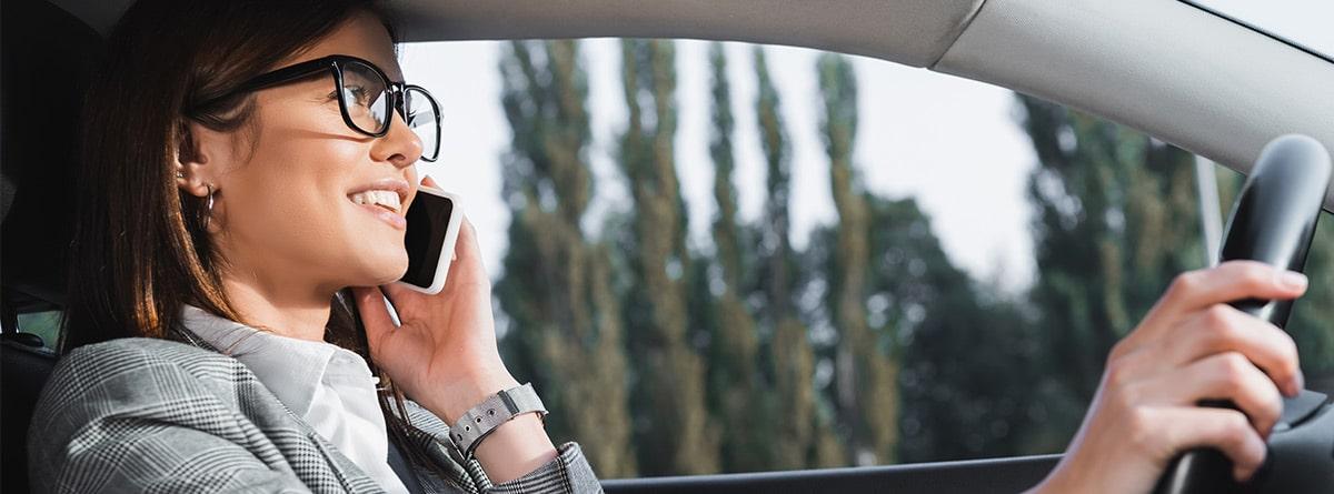 Mujer usando un teléfono móvil mientras conduce