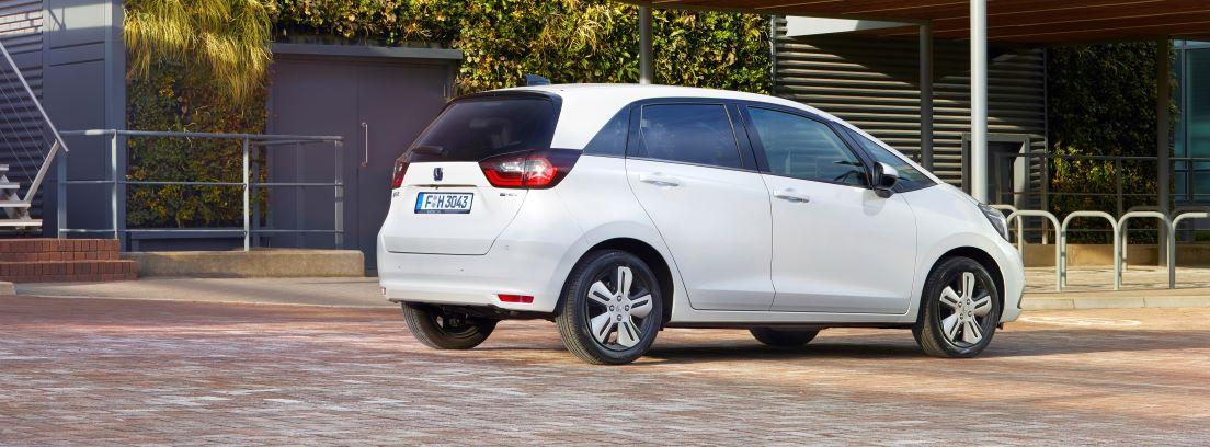Vista lateral/trasera del Honda Jazz e:HEV blanco parado en la calle