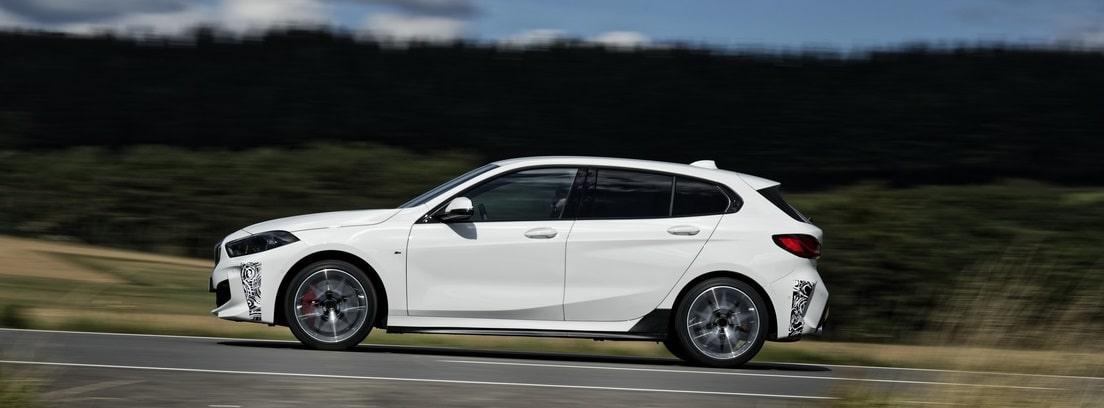 Vista lateral del nuevo BMW 128ti blanco circulando por una carretera