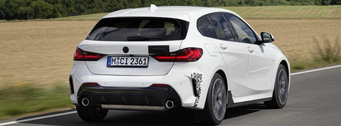 Vista trasera del nuevo BMW 128ti blanco circulando por una carretera