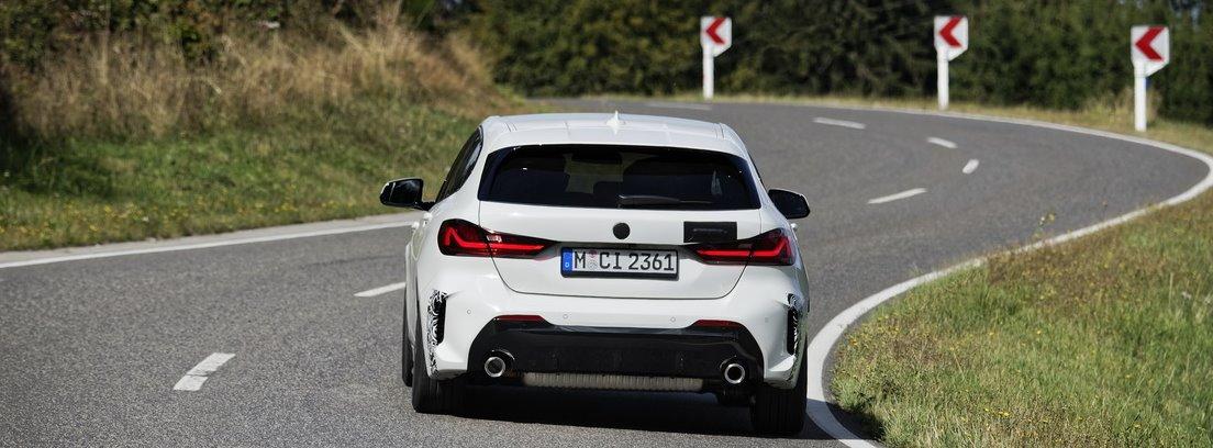 Vista trasera del nuevo BMW 128ti blanco entrando en una curva