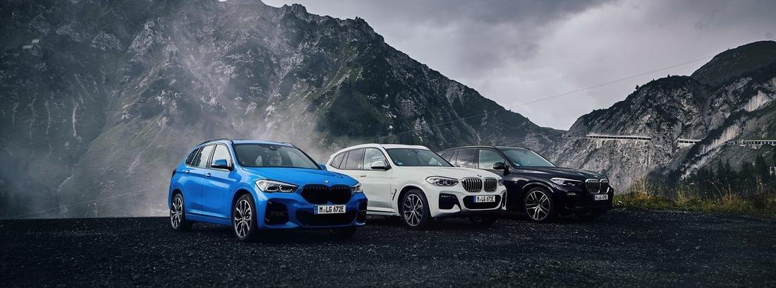 Tres coches BMW X1 xDrive25e en colores azul, blanco y negro parados entre montañas