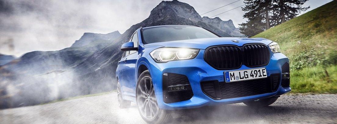 BMW X1 xDrive25e azul circulando parado en una carretera entre prados verdes y montañas