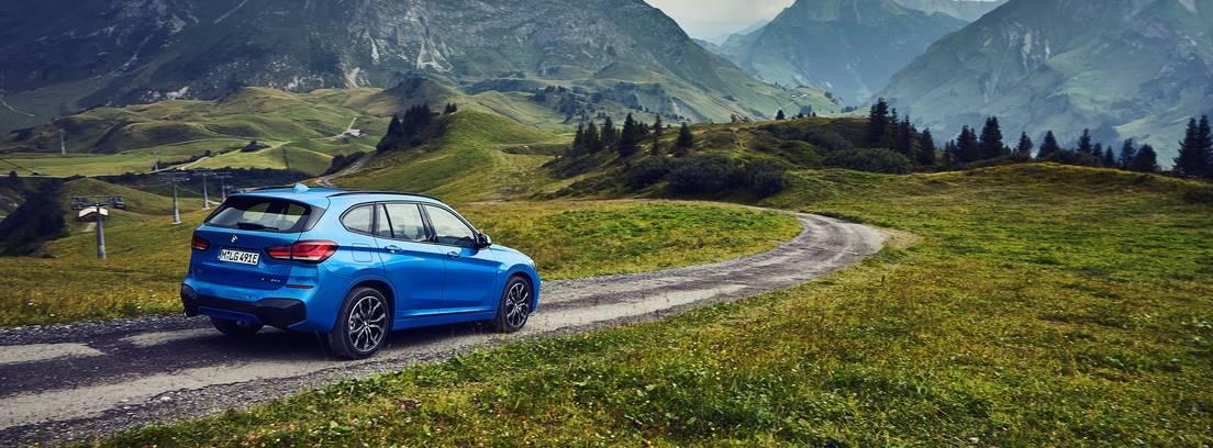 BMW X1 xDrive25e azul circulando por una carretera entre prados verdes
