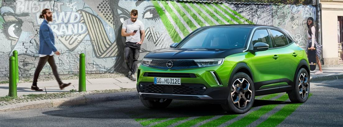 Opel Mokka-e verde aparcado en una calle con detalles destacados del mismo color que el coche