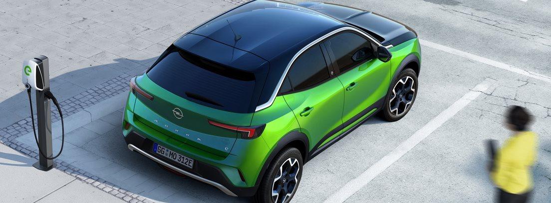 Vista elevada desde atrás del Opel Mokka-e verde estacionado junto a un cargador de coches eléctricos