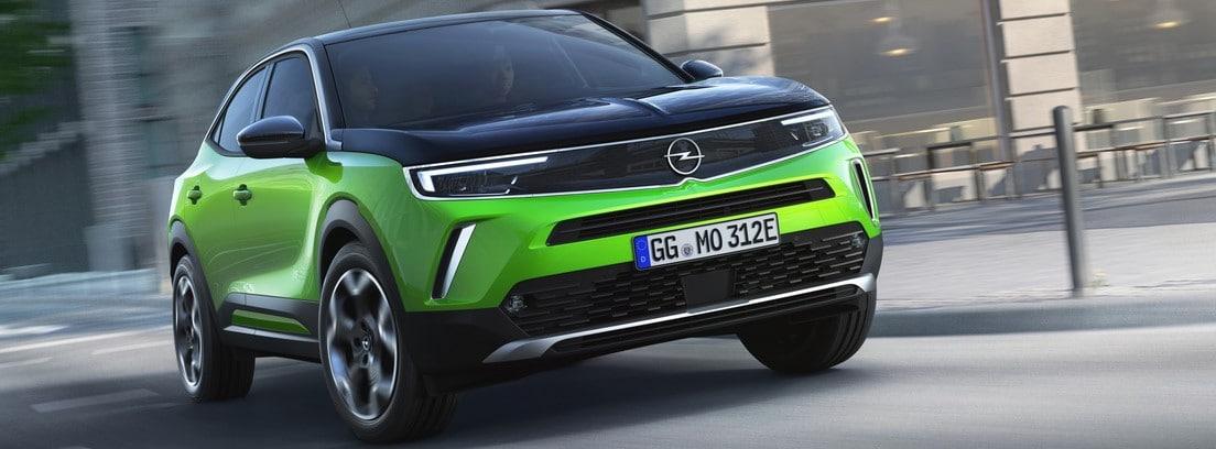 Vista frontal del Opel Mokka-e verde circulando por una ciudad