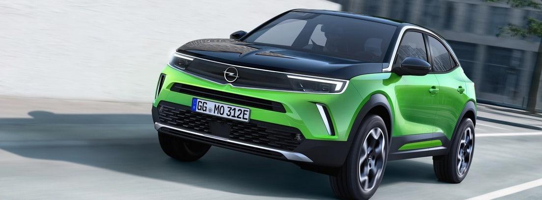 Vista delantera/lateral del Opel Mokka-e verde circulando por una ciudad