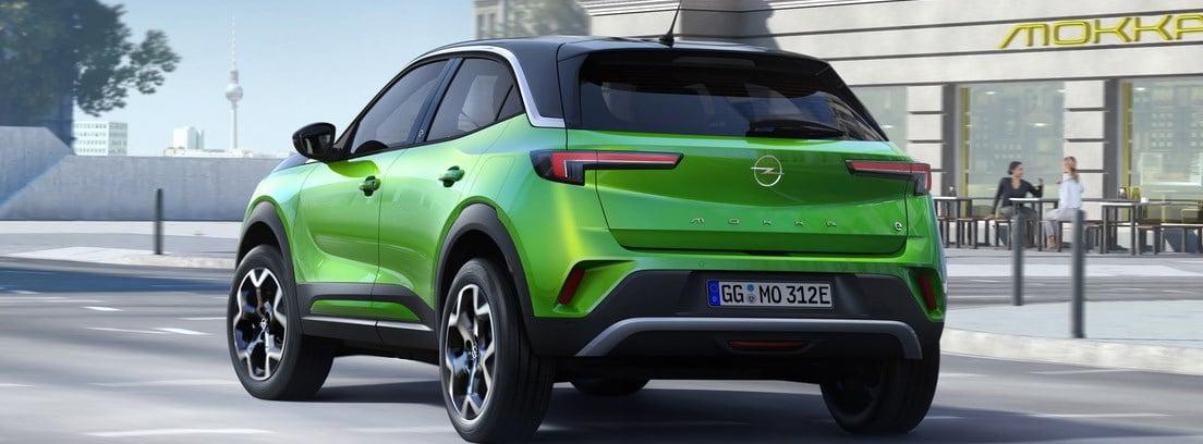 Vista trasera/lateral del Opel Mokka-e verde circulando por una ciudad