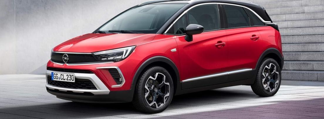 Nuevo Opel Crossland rojo aparcado bajo unas escaleras