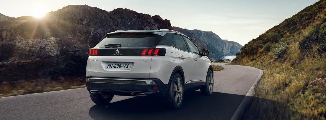 Vista trasera del Peugeot 3008 2020 en color blanco circulado por una carretera entre montes