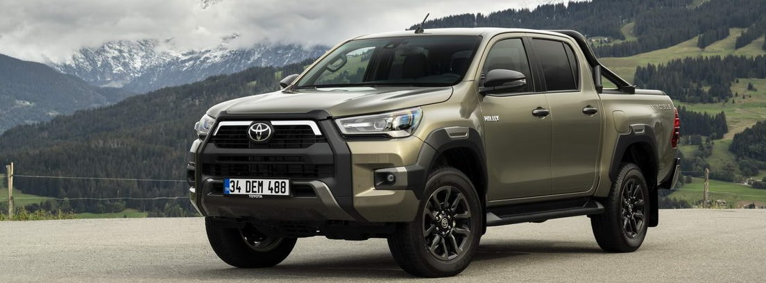 Nuevo Toyota Hilux 2021 parado con montañas verdes y nevadas de fondo