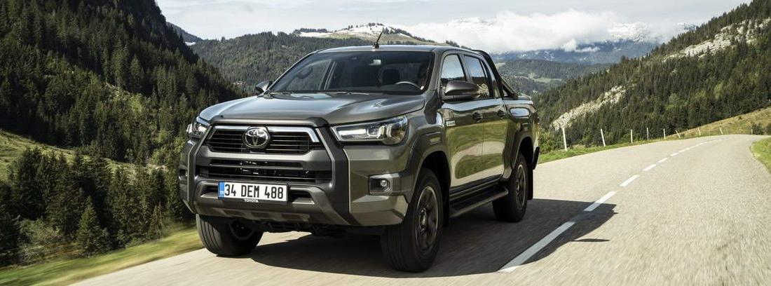 Nuevo Toyota Hilux 2021 circulando por una carretera rodeada de montañas verdes