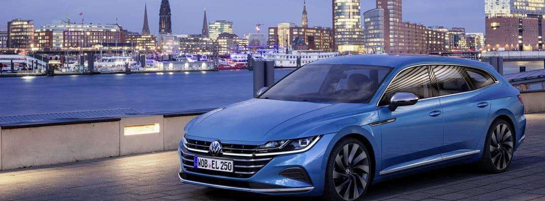 Volkswagen Arteon 2020 azul circulando cerca de un río con la ciudad iluminada de fondo