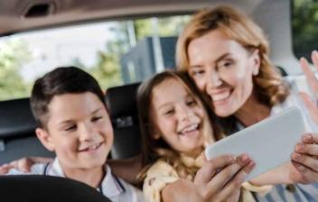 Mujer y dos niños en el asiento trasero de un coche