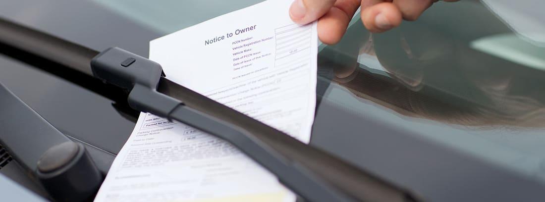 Mano recogiendo una multa de tráfico del parabrisas