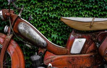 Ciclomotor antiguo aparcado en junto a un arbusto