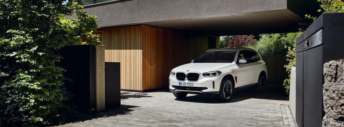 Nuevo BMW iX3 blanco aparcado bajo el porche de un chalet