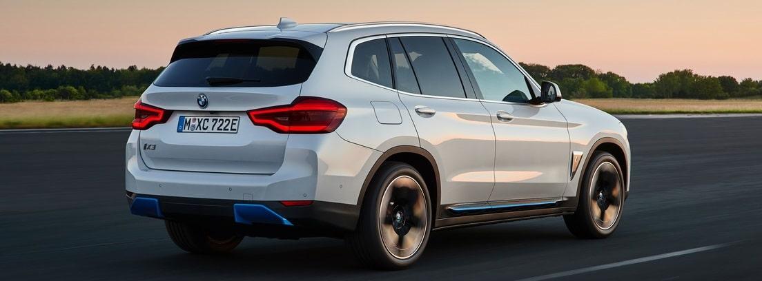 Vista trasera del nuevo BMW iX3 blanco circulando por una carretera